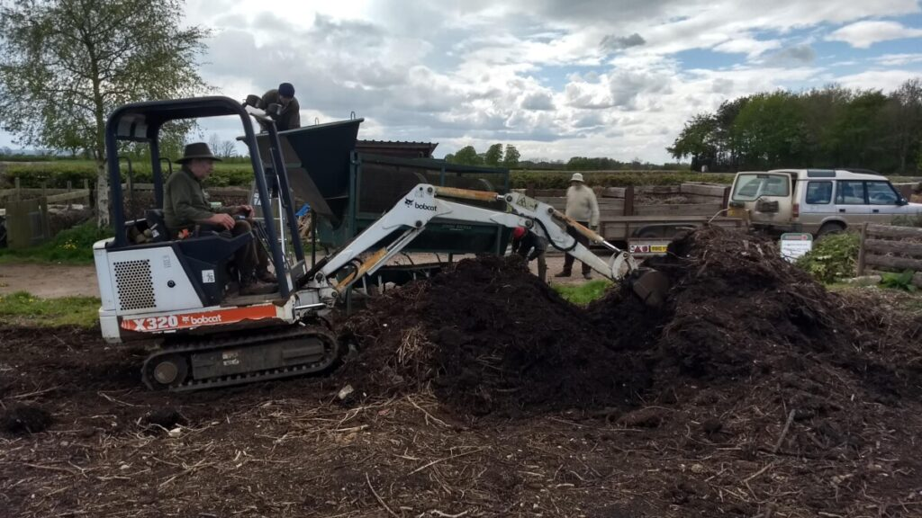 Mini digger and pile of compost at Bisley Community Composting Scheme